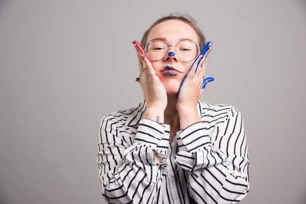 Женщина, касаясь ее лица руками краски на сером фоне
