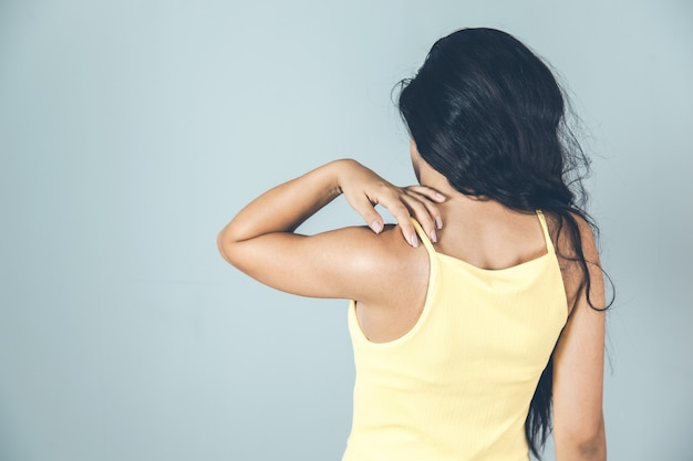 Женщина, касаясь ее шеи с болью в спине руки