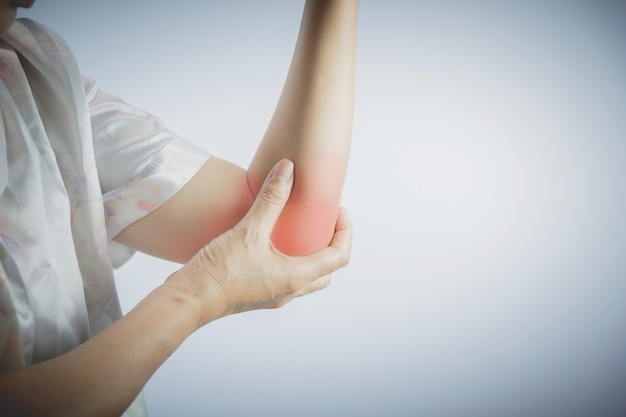 Woman touching her painful elbow. acute pain in a woman elbow.