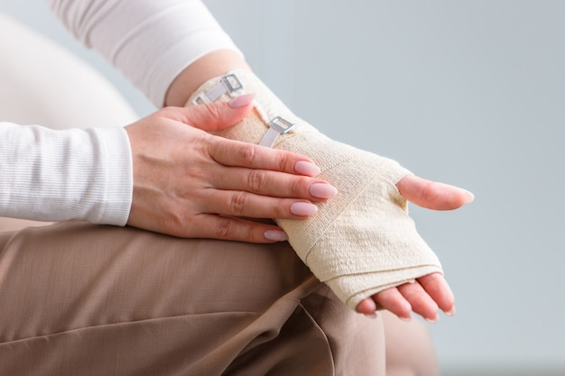 Woman touching her wrapped painful wrist with flexible elastic supportive orthopedic bandage after unsuccessful sports or injury, close up