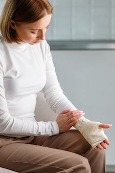 Woman touching her wrapped painful wrist with flexible elastic supportive orthopedic bandage after unsuccessful sports or injury