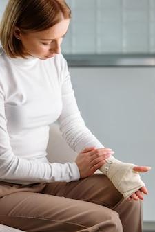 Женщина трогает ее обернутое болезненное запястье гибкой эластичной поддерживающей ортопедической повязкой после неудачных занятий спортом или травмы