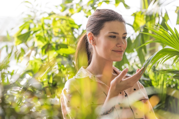 Woman touching plant in green house
