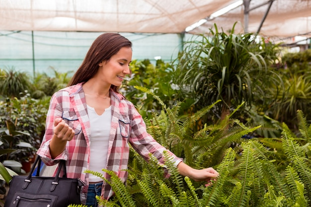 Woman touching plants in greenhouse