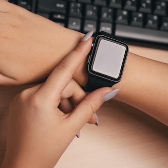 Woman touching smart watch hand on work desk.