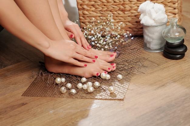 足の滑らかな肌に触れる女性