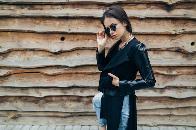 Женщина, касаясь солнцезащитные очки возле деревянной стены