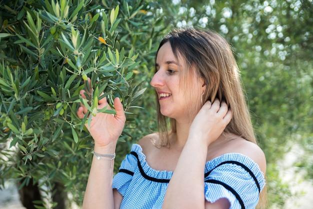 올리브 나무의 가지를 만지는 여자. 나무에 꽃이 만발한 올리브.