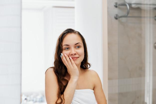 濡れた髪に触れて鏡を見ながら微笑む女性。コンディショナーとオイルを塗ったバスルームの女の子のポートレート。女性のポートレートは保護保湿クリームを使用しています。