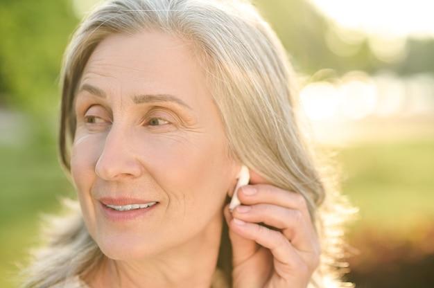 Woman touching wireless earphone in ear