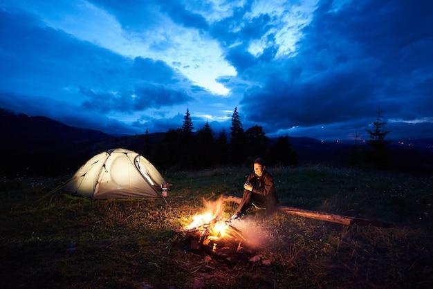 산에서 야영하는 밤에 여자 관광