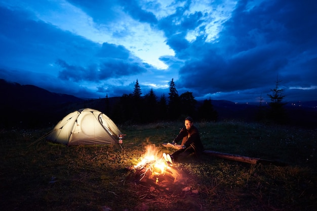 Женщина-турист в ночном кемпинге в горах