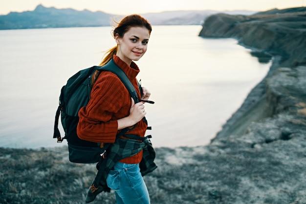 背中にバックパックを背負って山の海の近くの日没の女性観光客