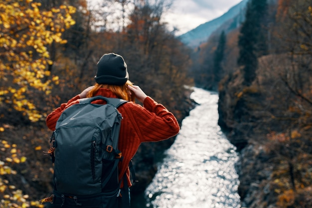 Woman tourist backpack river mountains autumn. high quality photo
