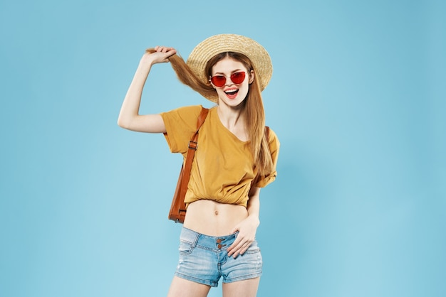 Женщина туристический рюкзак путешествия мода летняя одежда темные солнцезащитные очки синий фон