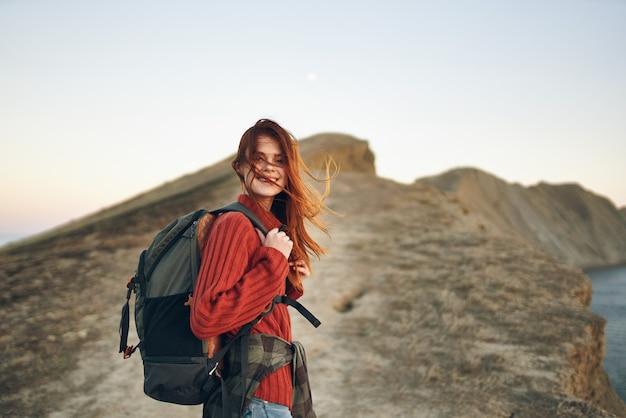 女性観光客は彼女の背中にバックパックを持って道路に沿ってバーの上部に登る