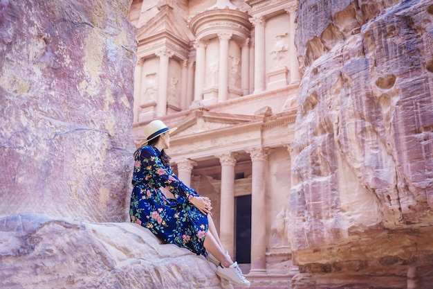 Woman tourist in color dress and hat enjoying the treasury, al khazneh in the ancient city of petra, jordan