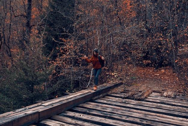 Женщина-турист пересекает мост через речное путешествие осенью