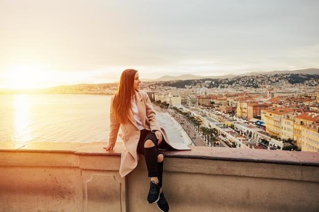 Туристическая женщина, наслаждающаяся закатом в ницце, франция.