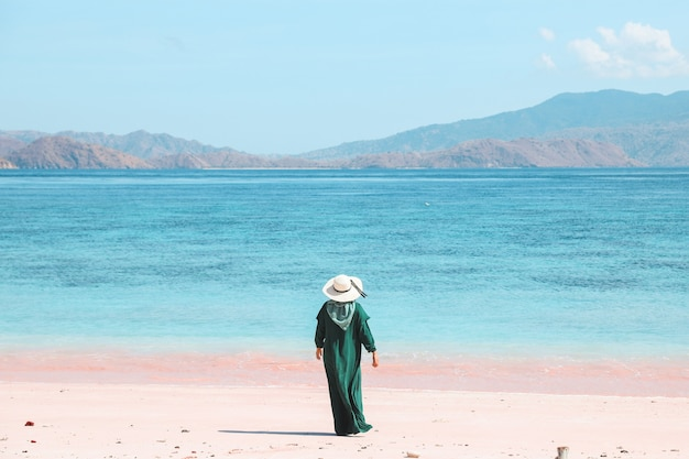 Woman tourist in green dress and summer hat standing on pink sandy beach enjoying at labuan bajo