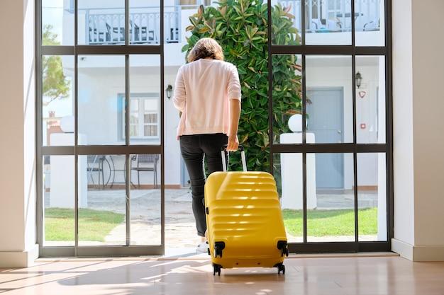 Гость женщины туристический с чемоданом в холле гостиницы, вид сзади. путешествие, отдых, туризм, досуг, люди выходного дня