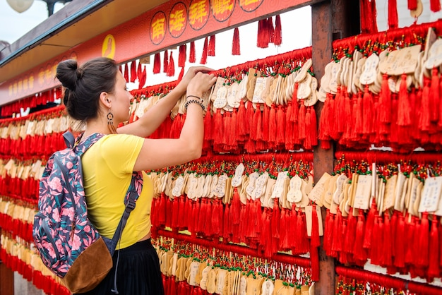 Woman tourist hangs wooden plank for writing prayers. chinese red and wooden plates for wishes. asian tradition.