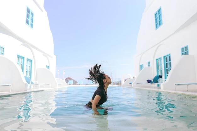휴가 기간 동안 수영장에서 물놀이를 즐기는 여성 관광객
