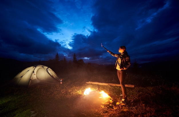 Woman tourist having a rest at night camping in the mountains, standing near burning campfire and illuminated tourist tent, pointing at evening cloudy sky