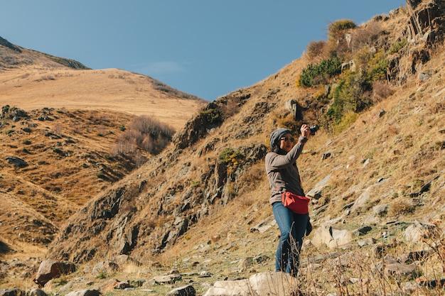 Woman tourist hiker travel through mountains trails.