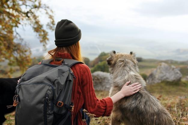 女性観光客は自然の中で犬を抱きしめます