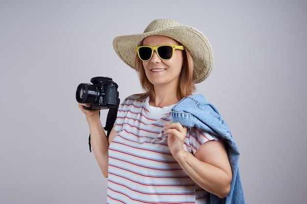 모자를 쓴 여성 관광객이 카메라를 사용하고 사진을 찍습니다. 회색 배경에 격리합니다.