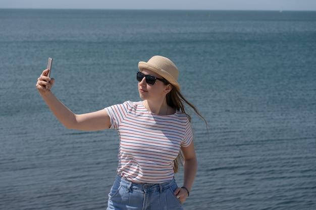 カジュアルな服装の女性観光客が海で携帯電話を使って自分撮りをします。海外で休む、海の空気。閉じる。