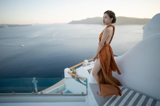 ギリシャのイアサントリーニ島の白塗りの村を訪れるゴージャスなドレスを着た女性観光客