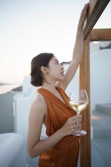 日没時にリラックスしたワインのグラスとゴージャスなドレスを着た女性観光客