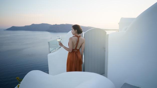 Женщина-турист в великолепном платье с бокалом вина, расслабляясь на закате