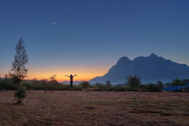 Турист женщины в силуэте стоит на траве в красивом небе
