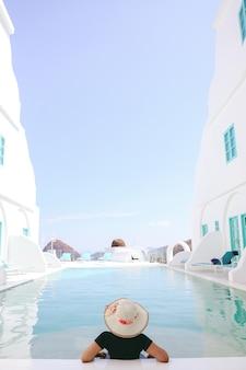 여름날 수영장에서 휴식을 취하는 여름 모자를 쓴 여성 관광객