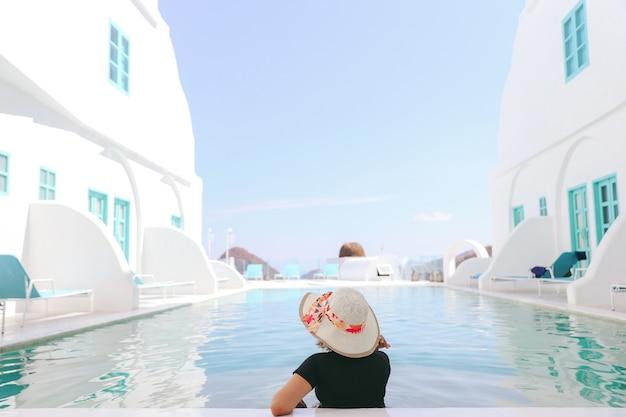 수영장에서 휴식을 취하는 여름 모자를 쓴 여성 관광객