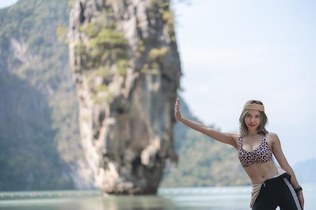 Туристическая женщина в купальнике позирует на острове джеймса бонда, пханг нга, таиланд.