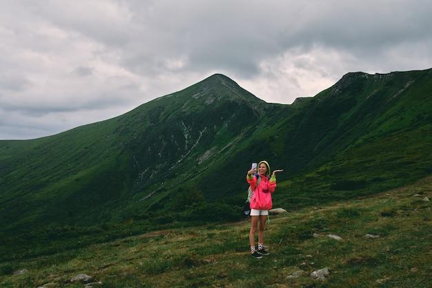 Туристическая женщина в горах, покрытых травой, делает селфи по телефону. горный пейзаж в тумане и пасмурную погоду. активный образ жизни, покорение вершин, свобода.