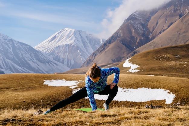 Женщина-турист занимается спортом на фоне гор