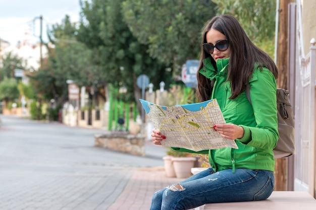여성 관광객이 도시의 거리에서 지도를 보고 있다