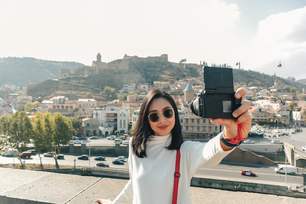 Woman tourist is taking selfie of herself and the view of tbilisi old town in georgia.