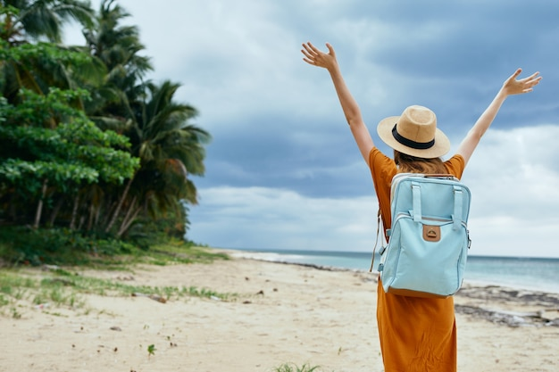 Woman tourist on the island hands raised up travel joy