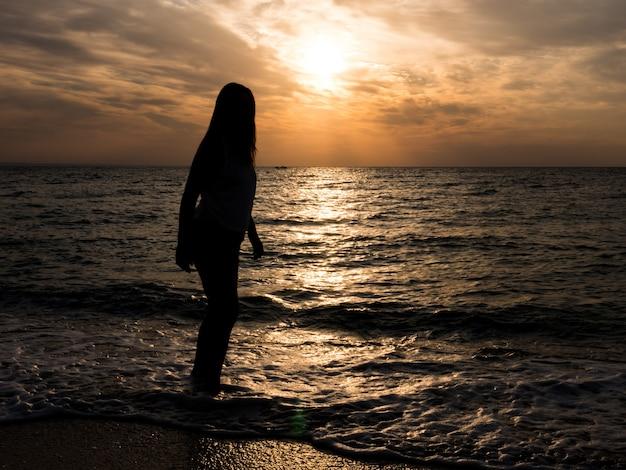 海に沈む夕日を眺める女性観光客。海でのリラクゼーション