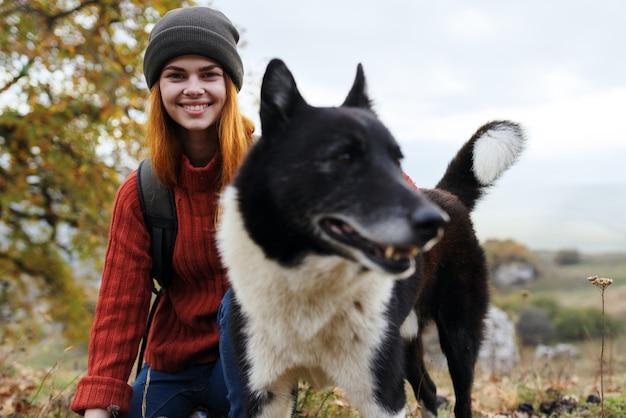 犬の隣の女性観光客は友情旅行の自然を抱きしめます