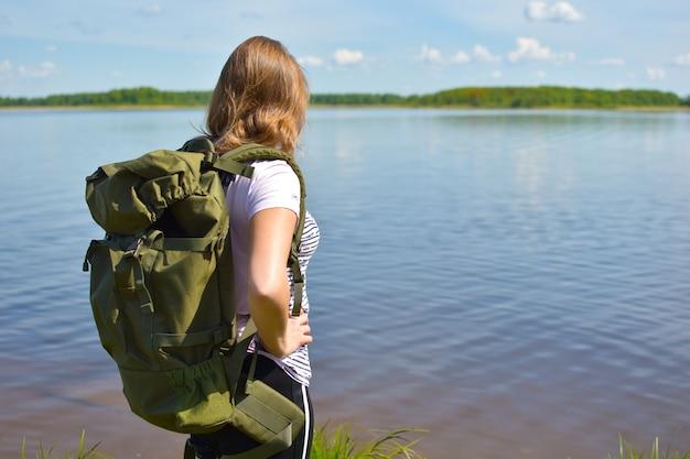 Женщина турист на озере с рюкзаком