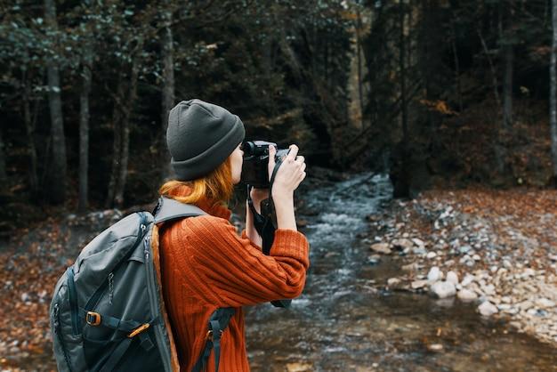 自然川の森の山々を撮影する女性観光客