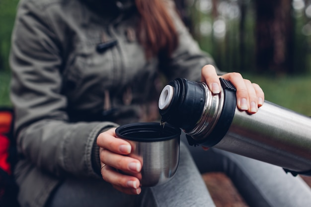 Woman tourist pours hot tea out of thermos in spring forest. camping, traveling and sport concept