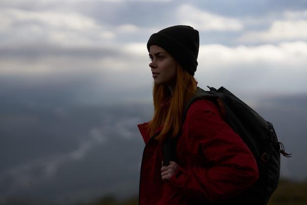 女性の観光客の買い物客は山の極端な新鮮な空気をバックパックします